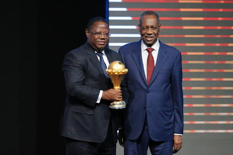 Gabonese Prime Minister Emmanuel Issoze Ngondet (L) holds the trophy next to Confederation of African Football (CAF) president Issa Hayatou during the 2017 African Cup of Nations draw ceremony on October 19, 2016 in Libreville (AFP Photo/Marco Longari)