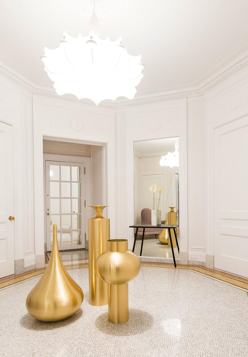 """This 5,000-square-foot five-bedroom apartment in the Apthorp, a landmarked New York City condominium built in 1908, was designed by Megan Grehl of Homepolish. The foyer shows off a trio of Tom Dixon's """"Beat"""" floor vessels, whose curvaceous shapes pair well with Marcel Wander's """"Mad"""" chaise lounge (seen in the mirror) and """"Zeppelin"""" light pendant."""