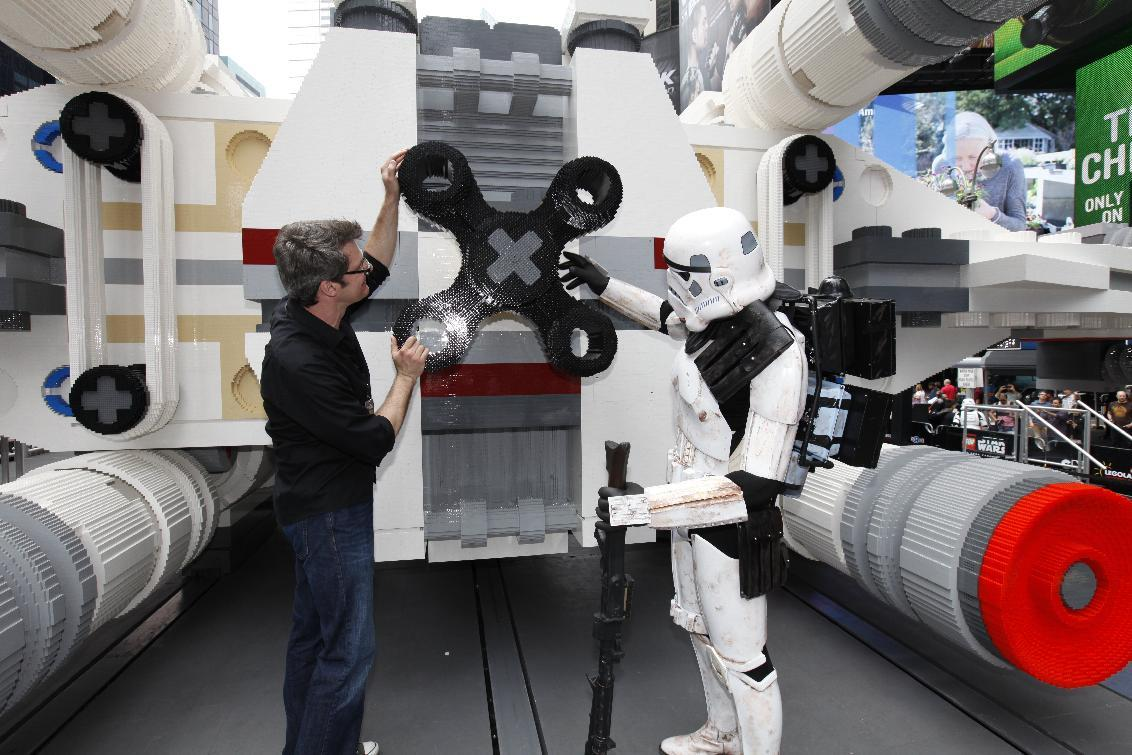 LEGO Master Builder Erik Varszegi and members of the 501st inspect the thrusters of the largest LEGO model ever built, an X-wing Starfighter made from 5.3 million LEGO bricks, upon its reveal in New York City's Times Square, Thursday May 23, 2013. (Amy Sussman/ AP Images for the Lego Group)