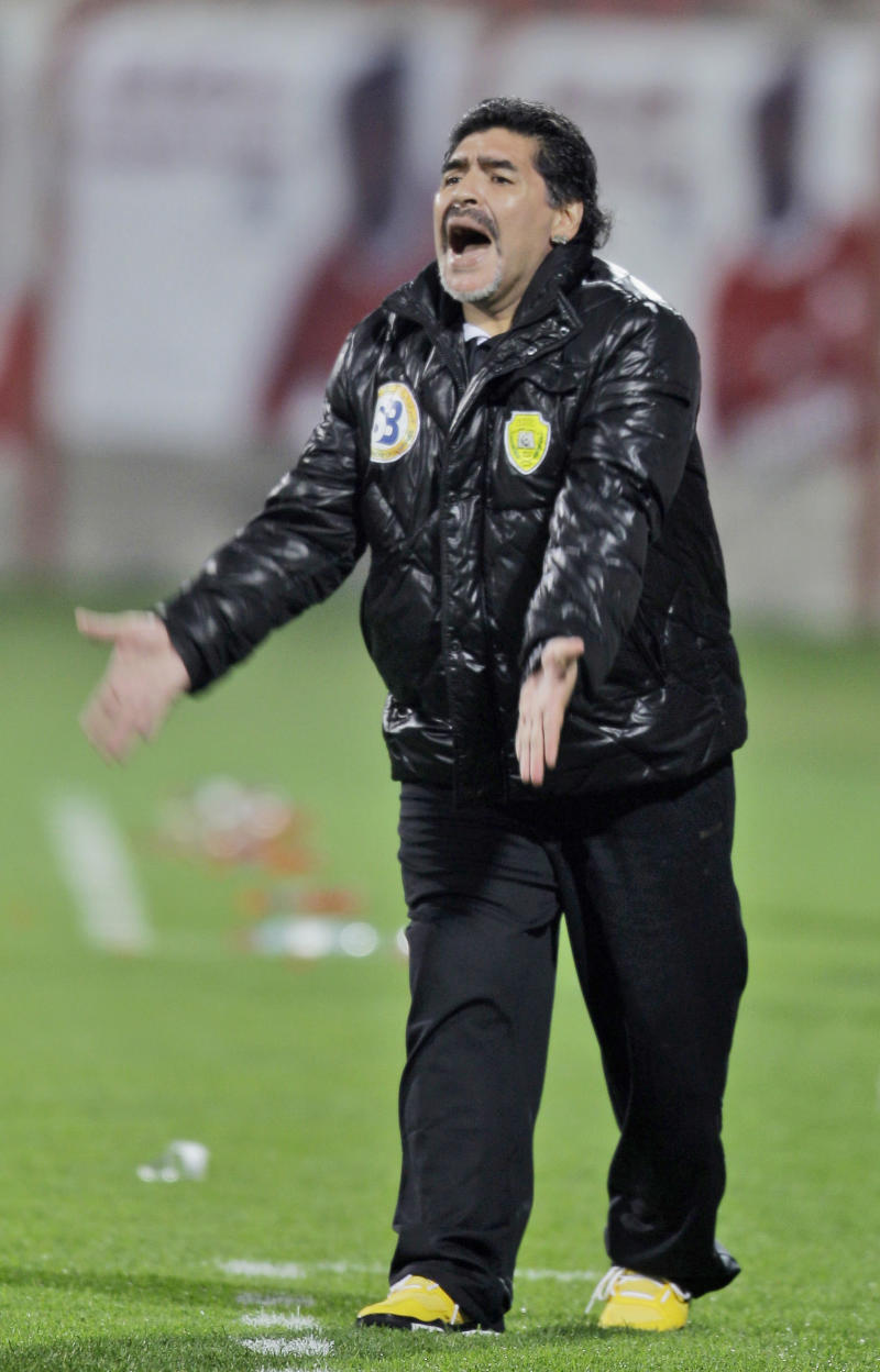 """FILE- In this file photo dated Sunday, March 11, 2012, Argentinean Diego Maradona, coach of the United Arab Emirates soccer team Al Wasl,  during a semi final match against Al Ahli, in Dubai, UAE.  Maradona is reported Friday March 30, 2012, to have been restrained by security staff as he confronted opposition fans in the stands on Thursday march 29, seemingly angry at threats and abuse allegedly directed toward wives and girlfriends of his Al Wasl players. Maradona is reported to ahve called the opposition Al Shabab fans """"cowards"""" after they heckled the women during his team's 2-0 loss.(AP Photo/Kamran Jebreili, FILE)"""