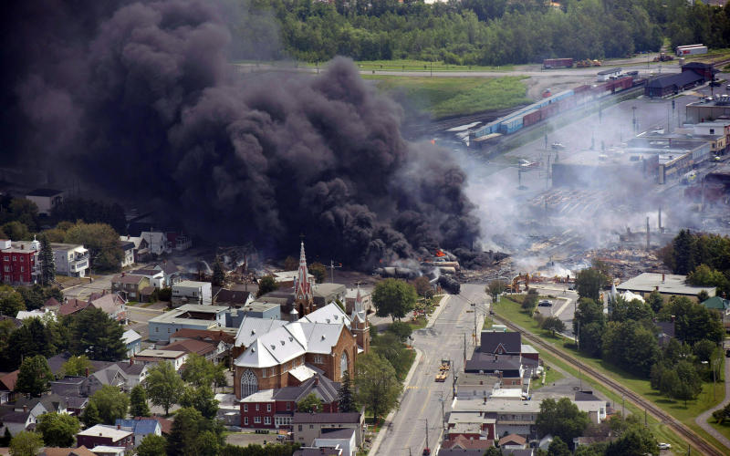 FILE - In this July 6, 2013 file photo, smoke rises from railway cars from now-defunct Montreal, Maine & Atlantic Railways company that were carrying crude oil after derailing in downtown Lac Megantic, Quebec. Forty-seven people were killed. The Trump administration is withdrawing a proposal for freight trains to have at least two crew members that was drafted in response to explosions of crude oil trains in the U.S. and Canada. Transportation officials said Thursday, May 23, 2019 that a review of accident data did not support the notion that having one crew member is less safe than a multi-person crew. (Paul Chiasson/The Canadian Press via AP, File)