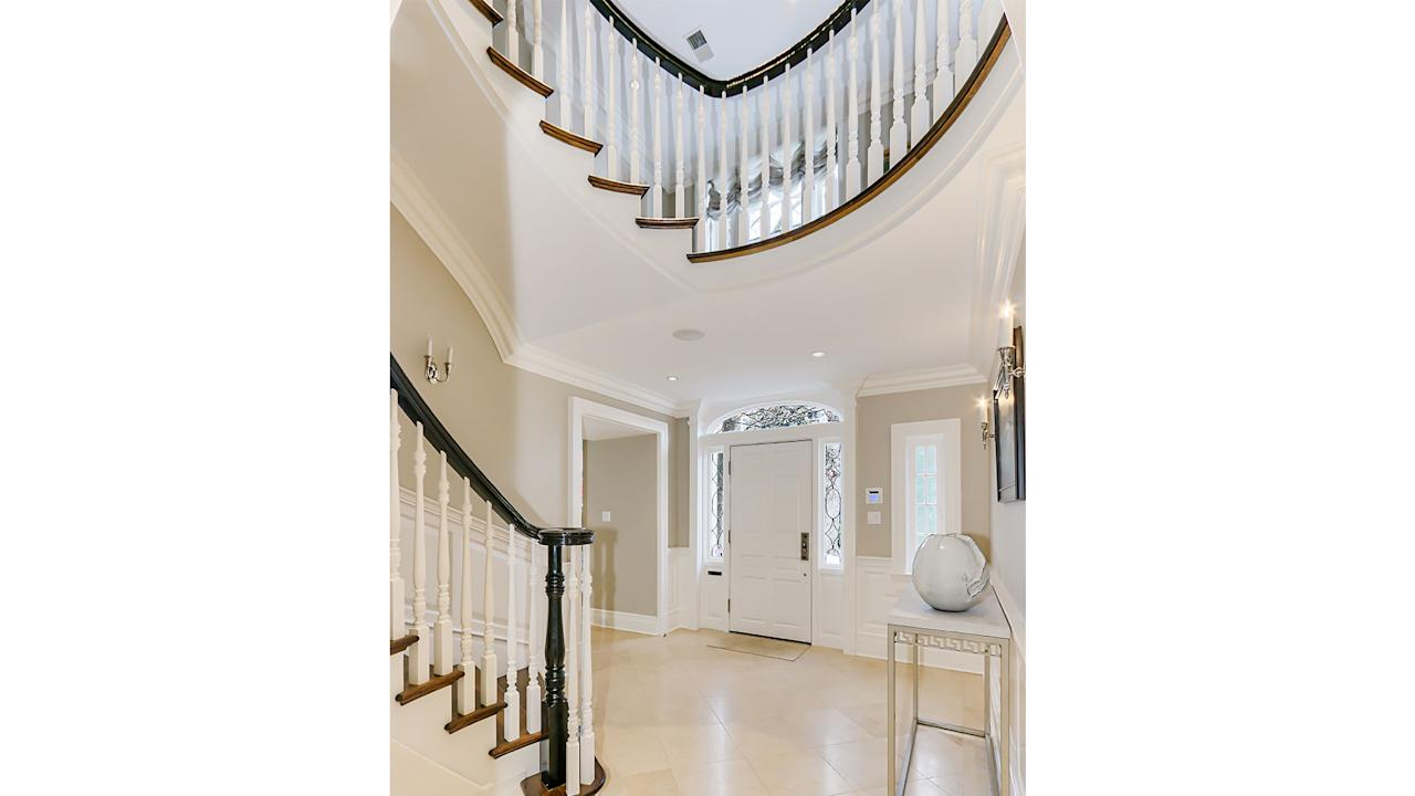 <p>A dark wood banister plays off the neutral tones in the soaring two-story entryway.</p>