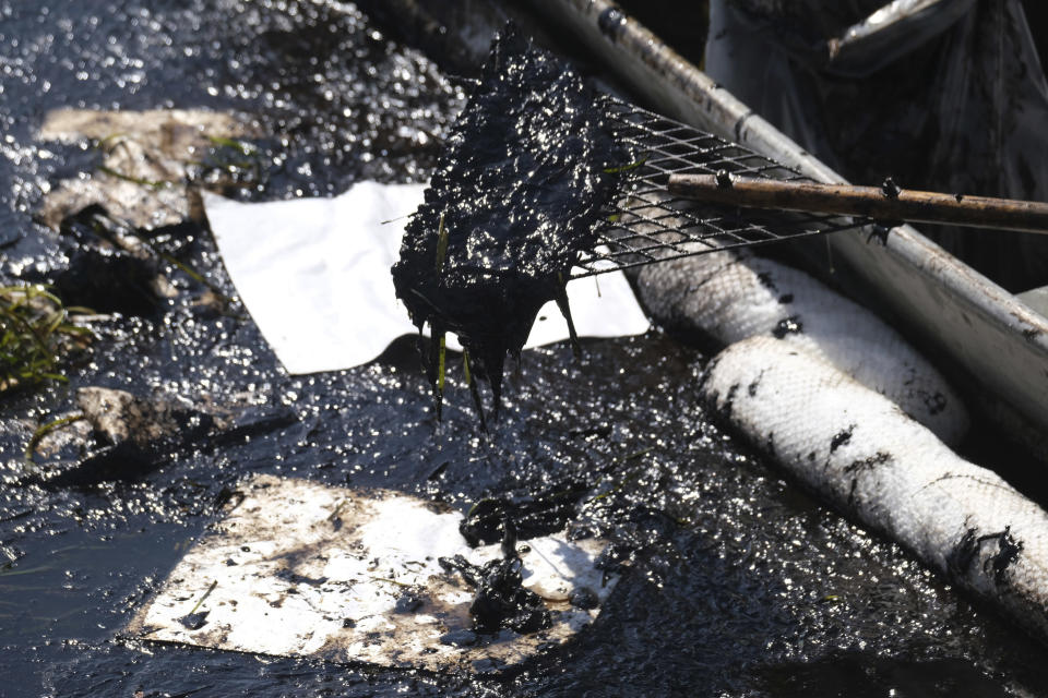 A cleanup contractor uses a skimmer after an oil spill in Huntington Beach, Calif., Sunday, Oct. 3, 2021. (AP Photo/Ringo H.W. Chiu)