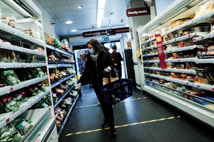 A woman wearing a mask and latex gloves shops in a branch of Sainsbury's in Bayswater, London, England. Photo: David Cliff/NurPhoto via Getty Images