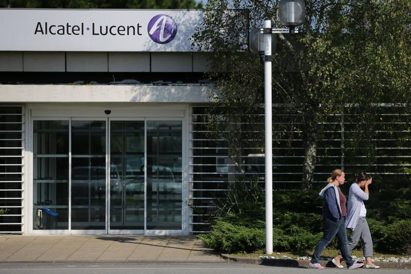 Employees of Alcatel-Lucent walk past an entrance at the company site in Orvault near Nantes