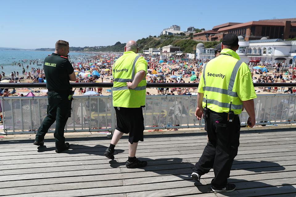 A member of the Ambulance Service walks with two security staff along Bournemouth Pier in Dorset as crowds gather on the beach below. (Photo by Andrew Matthews/PA Images via Getty Images)