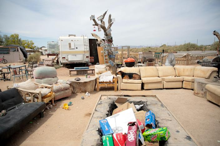 A dog sits on one of the couches outside at California Ponderosa camp in Slab City, Calif., on Monday, April 5, 2021.