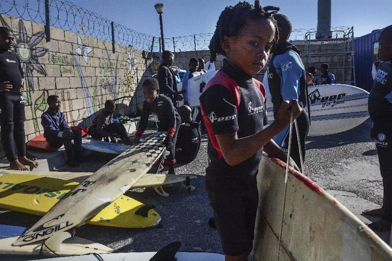 Children taking part in the Waves for Change programme get ready for a day of surfing at Monwabisi Beach, Khayelitsha, on August 7, 2014 (AFP Photo/Rodger Bosch)