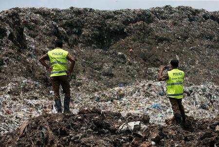 Sri Lankan crime police officers take pictures of the garbage dump during a rescue mission after a garbage dump collapsed and buried dozens of houses in Colombo, Sri Lanka April 16, 2017. REUTERS/Dinuka Liyanawatte