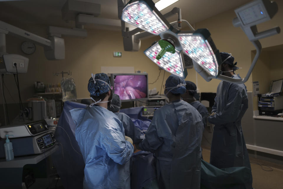 Medical staff work on the surgery of Lolita Andela at Bichat Hospital, AP-HP, in Paris, Wednesday, Dec. 2, 2020. After multiple false dawns, they scarcely dare believe that their Paris hospital, no longer overwhelmed by COVID-19 patients, is now once again able to perform their weight-reducing intestinal tucks. When the epidemic was burning through hospital resources, the women's operations were pushed back time and again. (AP Photo/Francois Mori)