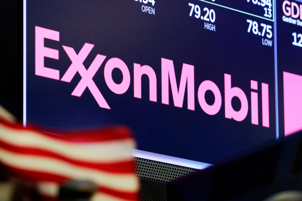 FILE - In this April 23, 2018, file photo, the logo for ExxonMobil appears above a trading post on the floor of the New York Stock Exchange. Exxon Mobil is slashing 1,900 jobs from its U.S. workforce as the pandemic continues to sap demand for fuel. The Irving, Texas-based oil giant said on Thursday, Oct. 29, 2020, the reductions will be both voluntary and involuntary and will largely come from its management offices in Houston. (AP Photo/Richard Drew, File)