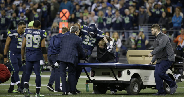 Seahawks running back Chris Carson (32) is held onto a cart after an injury. (AP)