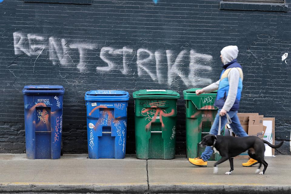 A pedestrian walks past graffiti in Seattle's Capitol Hill neighborhood. With millions of people suddenly out of work, some tenants in the U.S. have gone on a rent strike. Some cities have temporarily banned evictions, but advocates for the strike are demanding that rent payments be waived, not delayed, for those in need during the crisis. (Photo: Ted S. Warren/Associated Press)