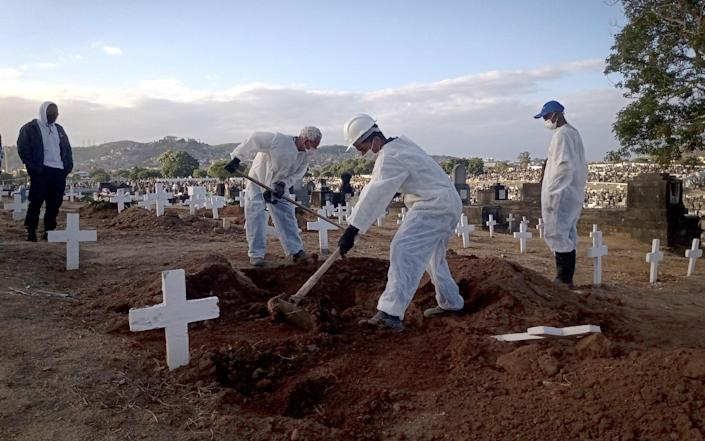 Funeral workers carry out burials of Covid-19 victims at Inhauma Cemetry in Rio de Janeiro, Brazil on 29 July 2021 - Anadolu/Anadolu Agency