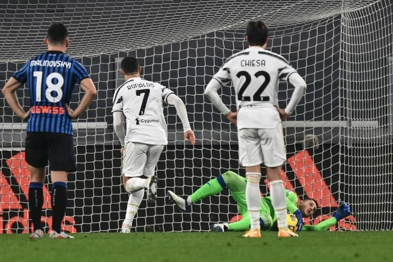 Atalanta goalkeeper Pierluigi Gollini (Rear Bottom) saves a Cristiano Ronaldo (2ndL) penalty in Turin.