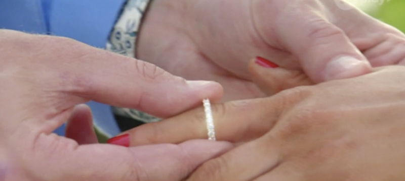 A close up of a man sliding a silver ring onto the finger of a woman on Bachelor In Paradise Australia 2020.