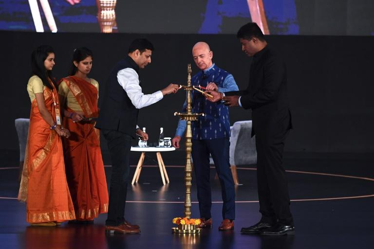 Amazon CEO Jeff Bezos (R) lights a traditional lamp along with Amit Agarwal (3L), senior vice president and country manager for Amazon India, at Amazon's Smbhav event in New Delhi