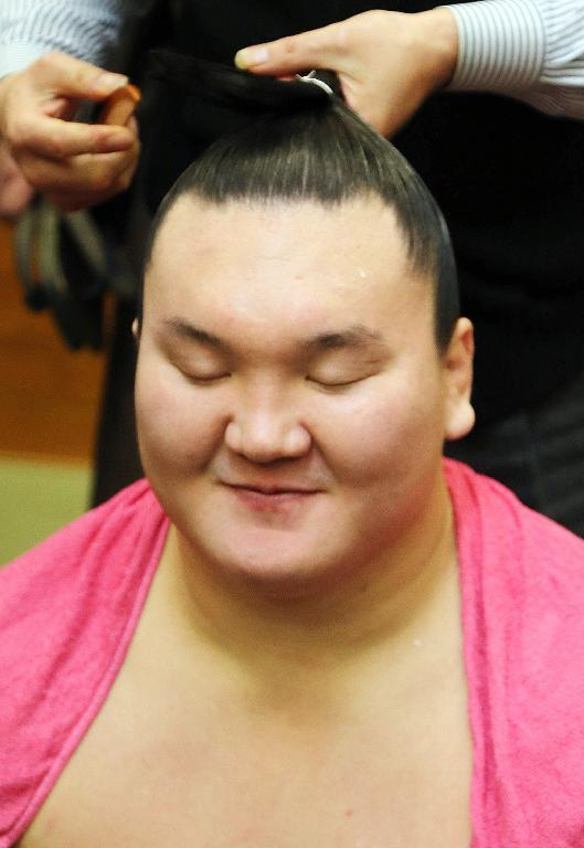 Mongolian-born yokozuna, or sumo grand champion, Hakuho smiles in the dressing room after earlier securing victory in the New Year Grand Sumo Tournament in Tokyo, on January 23, 2015