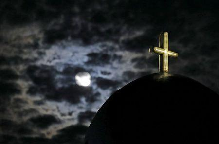 The moon rises above a church on the Greek island of Santorini, Greece, July 1, 2015. REUTERS/Cathal McNaughton