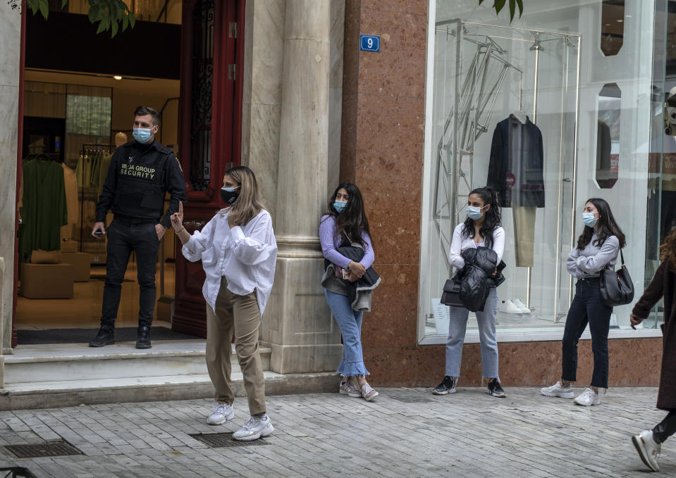 Customers wearing protective face masks queue outside a clothing store in Ermou street, central Athens, on Monday, April 5, 2021. Retail stores across most of Greece have been allowed to reopen despite an ongoing surge in COVID-19 infections, as the country battled to emerge from deep recession.(AP Photo/Petros Giannakouris)