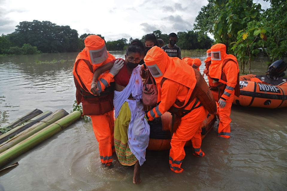 National Disaster Response Force (NDRF) personnel carry a sick woman during a rescue operation in a flood affected area due to monsoon rains, in Pathsala of Barpeta district, some 105 kms from Guwahati, the capital city of Indias northeastern state of Assam on July 12, 2020. (Photo by Biju BORO / AFP) (Photo by BIJU BORO/AFP via Getty Images)