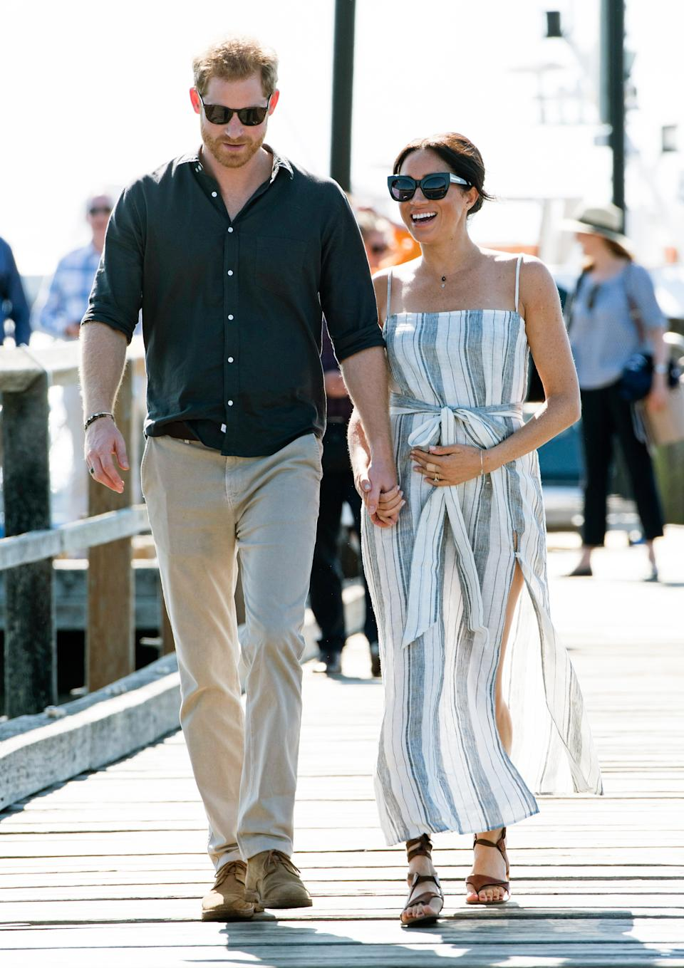Meghan opts for a striped Reformation dress during her visit to Fraser Island [Photo via Getty Images]