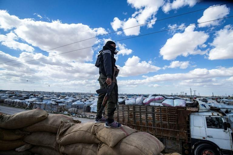 A member of the Kurdish internal security forces watches as a group of Syrian families is released in mid-March from the Kurdish-run Al-Hol camp