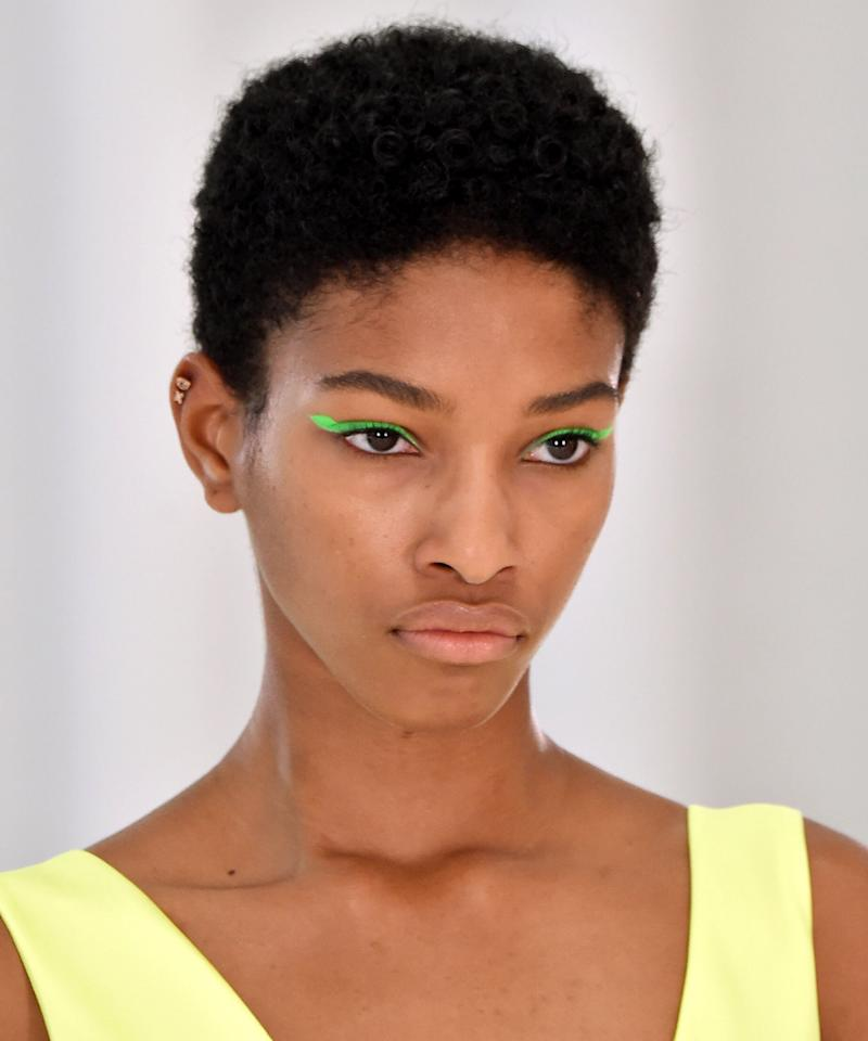 <p>A graphic flick of neon eyeliner is so striking, you can skip all other makeup and still be a knockout. At Helmut Lang, makeup artist Susie Sobol traced the wing shape first with white eye pencil and then brushed colored powder on top. </p>
