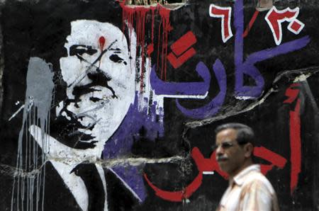 A man walks past graffiti depicting ousted Egyptian President Mursi in downtown Cairo