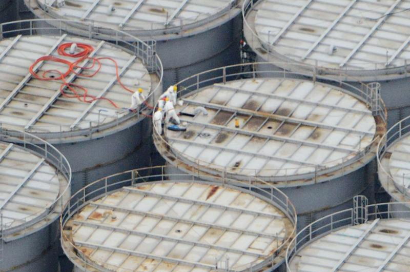 In this Tuesday, Aug. 20, 2013 aerial photo, workers stand on storage tanks at the Fukushima Dai-ichi nuclear plant at Okuma in Fukushima prefecture, northern Japan. The Japanese nuclear watchdog proposed Wednesday to define a fresh leakage of highly radioactive leak from one of the hundreds of storage tanks at Japan's crippled atomic power plant this week, its worst leak yet from such a vessel. The operator of the Fukushima Dai-ichi plant said Tuesday said about 300 tons (300,000 liters, 80,000 gallons) of contaminated water have leaked from a steel storage tank at the wrecked Fukushima Dai-ichi plant. TEPCO hasn't figured out how or where the water leaked, but suspects it did so through a seam on the tank or a valve connected to a gutter around the tank. (AP Photo/Kyodo News) JAPAN OUT, MANDATORY CREDIT