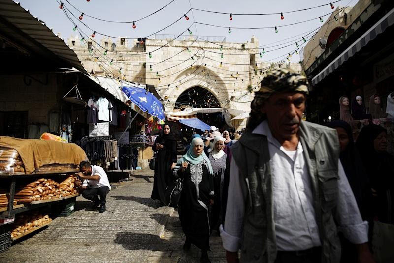 Palestinians walk past vendors as they enter through Damascus Gate in Jerusalem's Old City. (Photo: Nir Elias/Reuters)