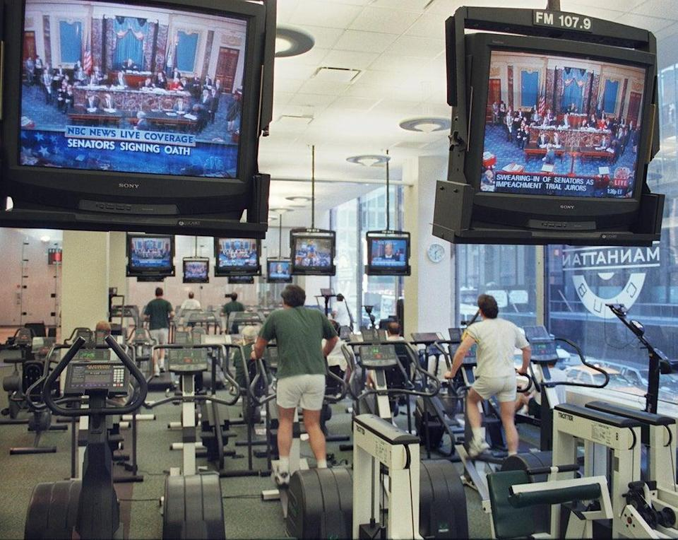 A group of people exercise on 7 January 1999 at the Manhattan Athletic Club in New York as they watch a live television broadcast of the impeachment trial of US President Bill Clinton (STAN HONDA/AFP via Getty Images)