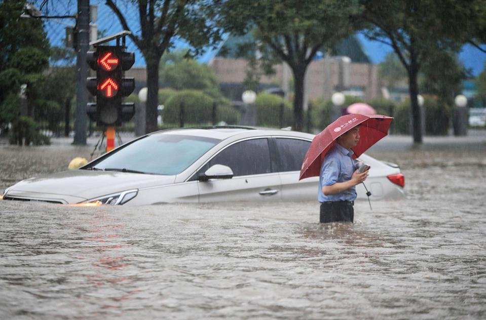A man wades past a submerged car along a flooded street following heavy rains in Zhengzhou on Tuesday (AFP via Getty Images)