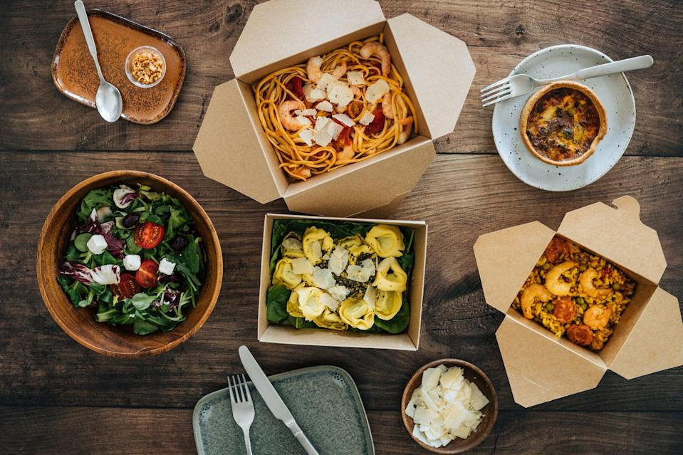 Flat lay view of delicious takeaway meals on dinner table - with pasta, vegetable salad and seafood risotto.