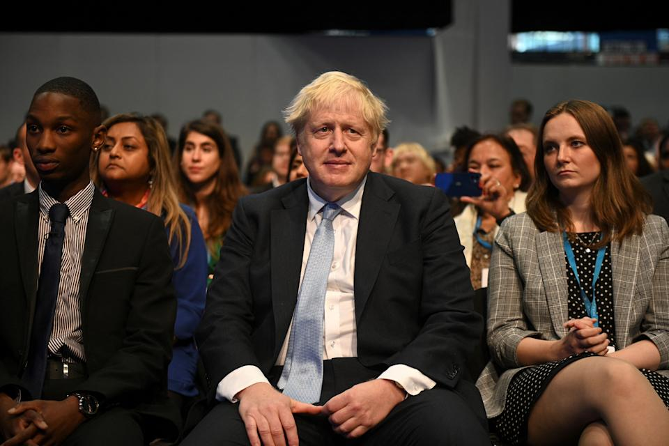 Britain's Prime Minister Boris Johnson (C) attends the second day of the annual Conservative Party Conference being held at the Manchester Central convention centre in Manchester, northwest England, on October 4, 2021. (Photo by Oli SCARFF / AFP) (Photo by OLI SCARFF/AFP via Getty Images)