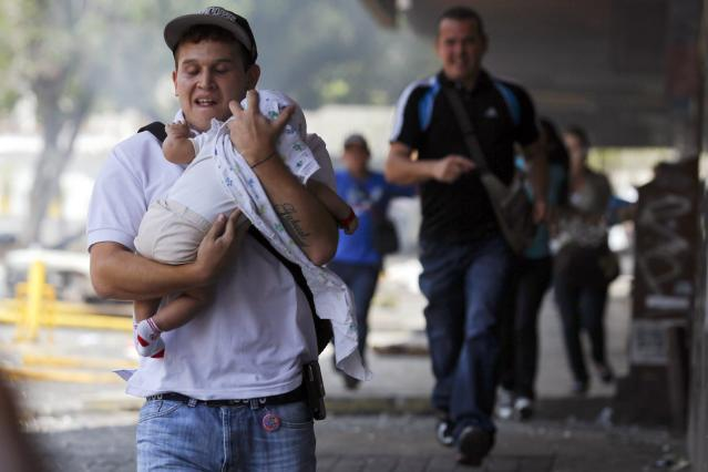 A man runs with a baby to take cover from teargas and stones during riots in Caracas March 6, 2014. A Venezuelan soldier and a motorcyclist were killed in a standoff with opposition demonstrators who had set up a barricade along an avenue of Caracas, the vice president of the ruling Socialist Party said on Thursday. Demonstrators demanding the resignation of President Nicolas Maduro have for weeks been staging rallies and setting up barricades, leading to clashes with security forces and government supporters. At least 20 have been killed. REUTERS/Carlos Garcia Rawlins (VENEZUELA - Tags: POLITICS CIVIL UNREST)