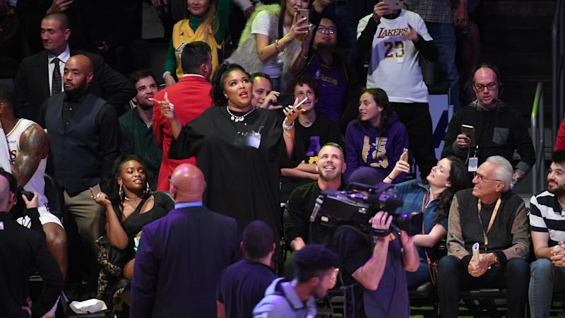 A photo of Lizzo wearing a black dress at a basketball game between the Los Angeles Lakers and the Minnesota Timberwolves at Staples Center on December 08, 2019 in Los Angeles, California