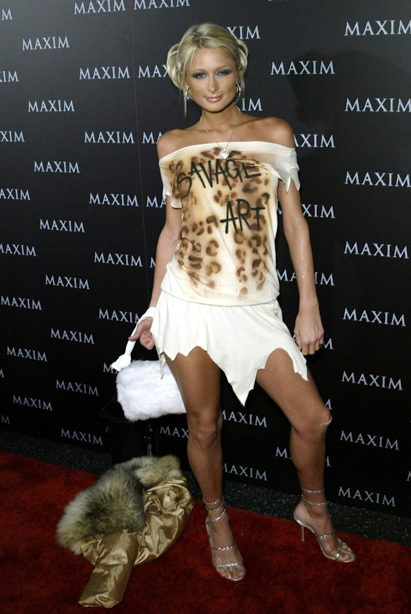"""Paris Hilton discards her fur coat to show off a """"Savage art"""" top while at a performance of The Pussycat Dolls in Hollywood."""