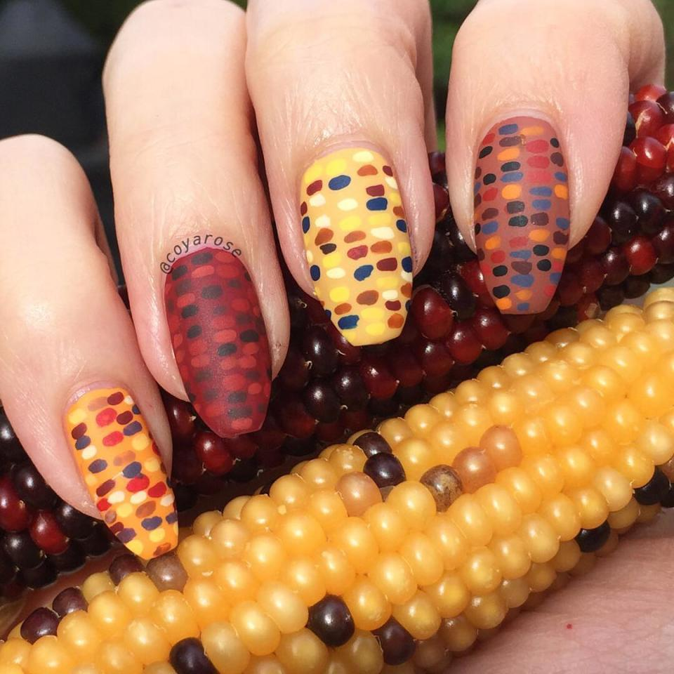 """We love this interpretation of the corn on the cob because while it's quite literal, it's not, well, corny. Nail-art hobbyist Nicoya Grobman share her matte take on the idea, hand-painting little kernal-like dots on the base shades <a href=""""https://www.amazon.com/Sinful-Colors-Nail-Polish-ANCHORS/dp/B00DW81MH2"""" rel=""""nofollow"""">Anchors Away by Sinful Colors</a>, <a href=""""https://www.amazon.com/Sally-Hansen-Xtreme-Effect-Poetic/dp/B00OR0ULEY"""" rel=""""nofollow"""">Wax Poetic by Sally Hansen</a>, <a href=""""https://inmnails.com/shop/nail-lacquer/beesknees/"""" rel=""""nofollow"""">Bees Knees by INM</a>, and <a href=""""https://www.amazon.com/Revlon-Nail-Enamel-Totally-Toffee/dp/B004K0KYD4"""" rel=""""nofollow"""">Totally Toffee by Revlon</a>."""