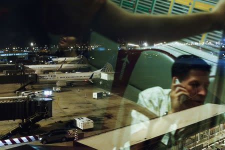 United Airlines planes are seen from the window of an airtrain as passengers are reflected in the glass at Newark International Airport in New Jersey