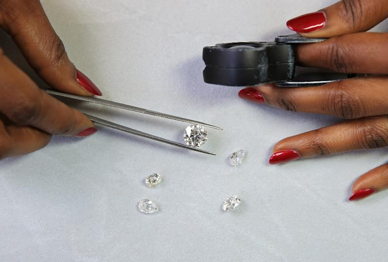Nigerian-Jewish diamond cutter and dealer, Thelma West, holds a cut diamond, valued at GBP 100,000, in her office in central London on March 11, 2016 (AFP Photo/Daniel Leal-Olivas)