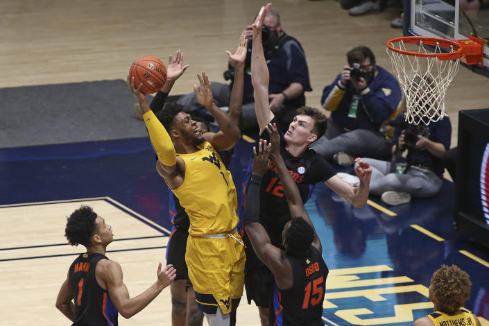 West Virginia forward Derek Culver (1) shoots while defended by Florida forward Colin Castleton (12) during the second half of an NCAA college basketball game Saturday, Jan. 30, 2021, in Morgantown, W.Va. (AP Photo/Kathleen Batten)