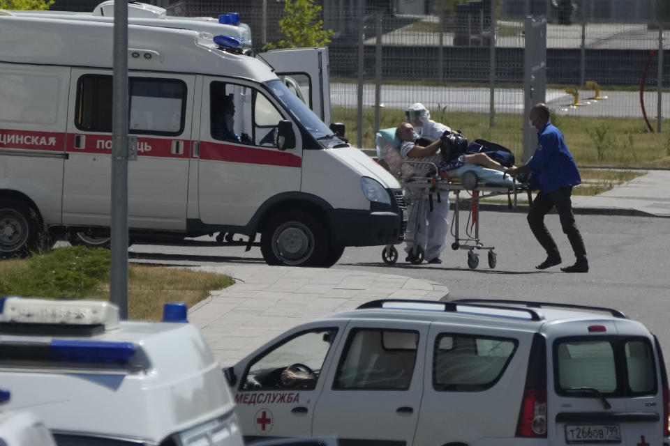 FILE - In this Monday, July 12, 2021 filer, a medical worker wearing protective gear escorts a man, suspected of having coronavirus, at a hospital in Kommunarka, outside Moscow, Russia. Russia has reported a record daily death toll from COVID-19. It's the fifth time in a week that deaths have hit a new high in the country. The national coronavirus task force said Sunday, Oct. 3, 2021 that 890 deaths were recorded over the past day. That exceeds the 887 reported on Friday. (AP Photo/Pavel Golovkin, File)