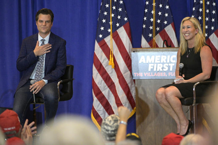 Rep. Matt Gaetz, R-Fla., left, and Rep. Marjorie Taylor Greene, R-Ga., address attendees of a rally, Friday, May 7, 2021, in The Villages, Fla. (AP Photo/Phelan M. Ebenhack)