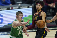Boston Celtics' Payton Pritchard (11) passes the ball around Cleveland Cavaliers' Brodric Thomas (33) during the first half of an NBA basketball game Wednesday, May 12, 2021, in Cleveland. (AP Photo/Tony Dejak)