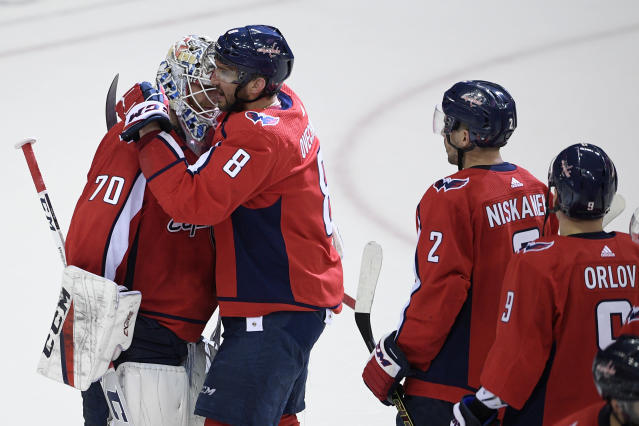 Washington Capitals left wing Alex Ovechkin (8), of Russia, celebrates with goaltender Braden Holtby (70) after Game 5 of an NHL hockey first-round playoff series against the Carolina Hurricanes, Saturday, April 20, 2019, in Washington. Also seen are Matt Niskanen (2) and Dmitry Orlov (9), of Russia. The Capitals won 6-0. (AP Photo/Nick Wass)
