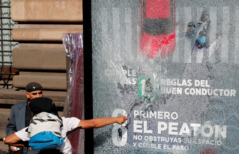A demonstrator smashes the glass of a billboard during a march marking the 51st anniversary of the 1968 student massacre by Mexican armed forces, in Mexico City, Mexico October 2, 2019. REUTERS/Henry Romero