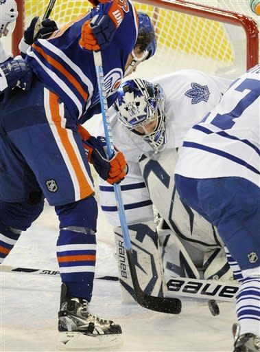 Edmonton Oilers' Ryan Jones, left, works against Toronto Maple Leafs goalie James Reimer during the first period of an NHL hockey game in Edmonton, Alberta, on Wednesday, Feb. 15, 2012. (AP Photo/The Canadian Press, John Ulan)