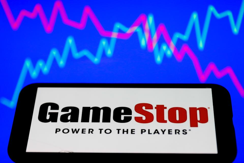 GameStop logo displayed on a phone screen and a illustrative stock chart on the background are seen in this illustration photo taken in Poland on January 28, 2021. In the last days the GameStop stock short squeeze continues. (Photo illustration by Jakub Porzycki/NurPhoto via Getty Images)