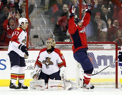 Florida Panthers center Marcel Goc (57) and goalie Jose Theodore (60) watch as Washington Capitals left wing Troy Brouwer (20), right, celebrates his assist to center Brooks Laich, not pictured, during the second period of an NHL hockey game on Thursday, April 5, 2012, in Washington. (AP Photo/Evan Vucci)